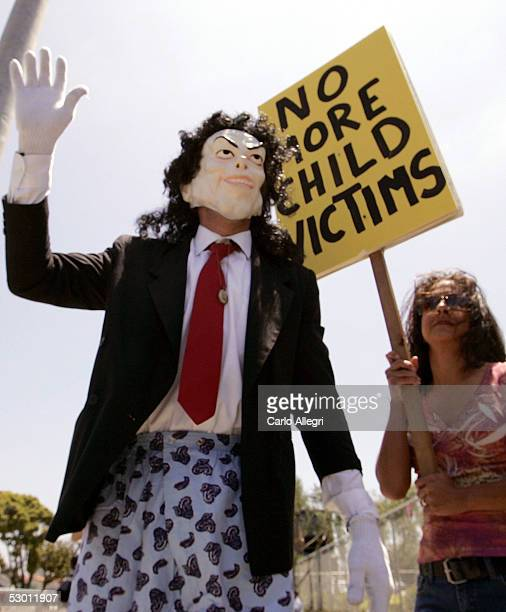 A person dressed like Michael Jackson waves toward fans at the Michael Jackson child molestation trial at the Santa Barbara County Courthouse June 2...