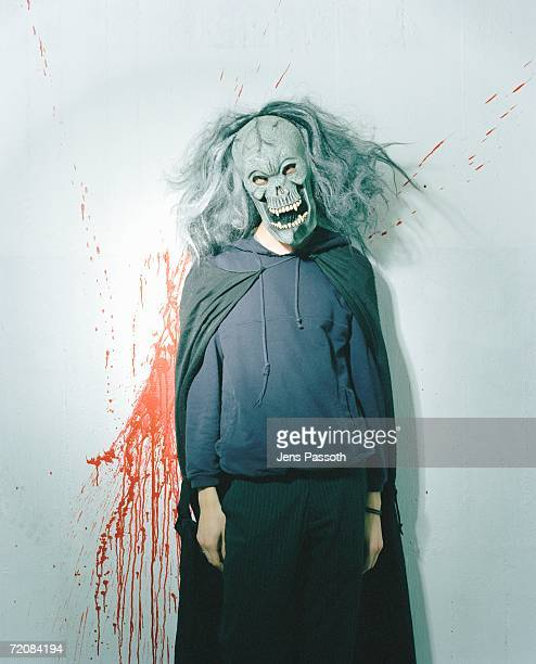 person dressed up in spooky mask and wig in front of blood splattered wall - shock tactics stock pictures, royalty-free photos & images