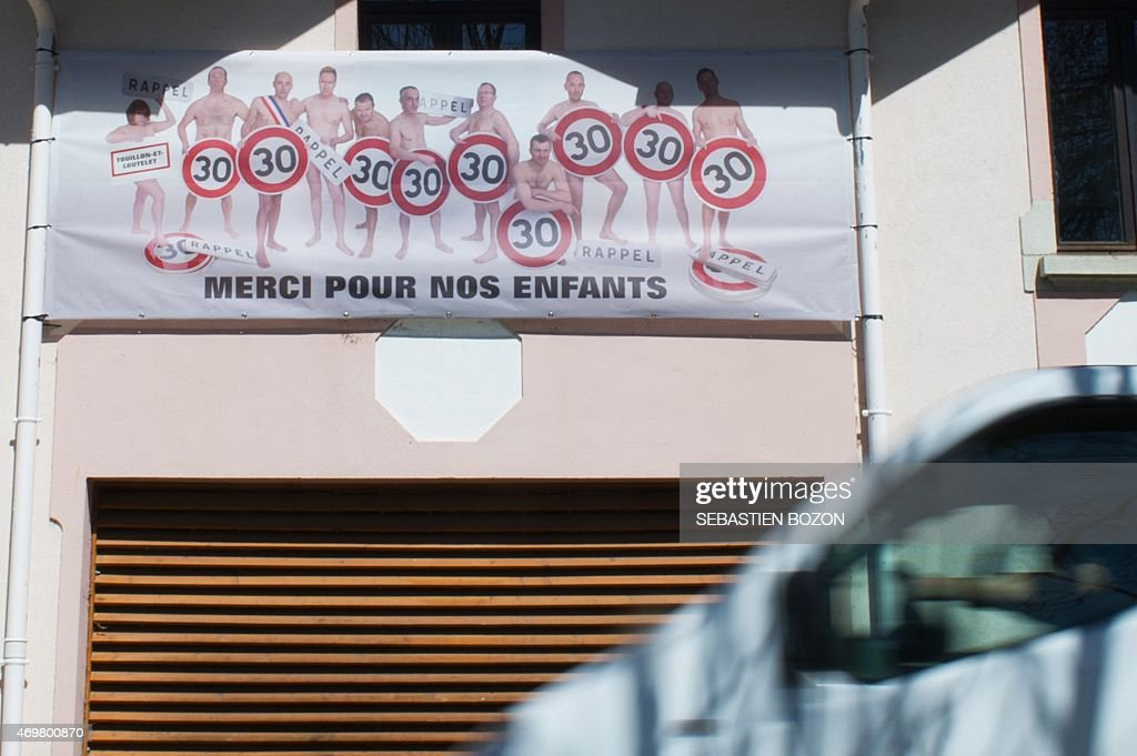 A person drives a truck in front of a banner showing members of the local council only wearing a speed limitation sign on their pelvis and a slogan reading 'Thanks for our children' to promote the new speed limitation in the village of Touillon-et-Loutelet, eastern France, on April 15, 2015. The local council has decided to reduce the speed from 50km/H to 30 in the village.