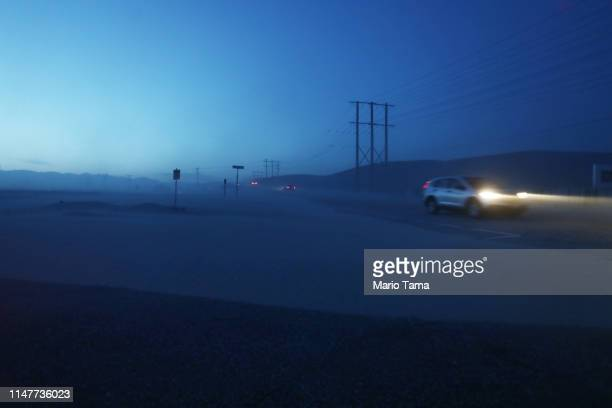 A person drives at dusk as sand blows along a road near a wind farm in the Coachella Valley on May 7 2019 in Palm Springs California California's...