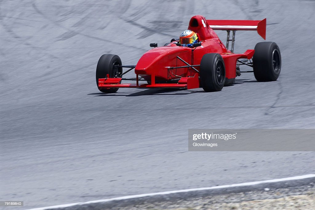 Person driving a formula one racing car on a motor racing track : Stock Photo