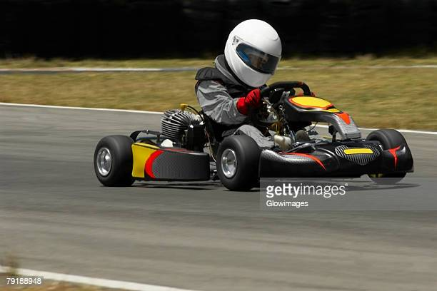 Person driving a go-cart on a motor racing track