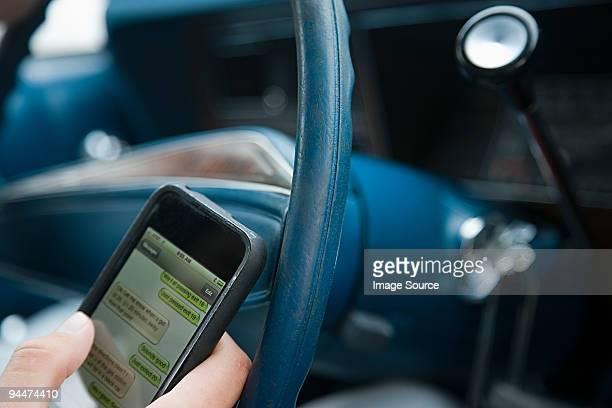 person driving and using cellphone - abgelenkt stock-fotos und bilder