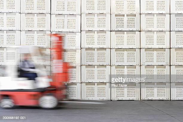 person driving forklift beside stack of crates - gabelstapler stock-fotos und bilder