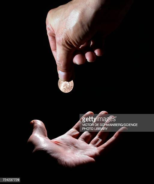 Person dropping coin on palm of hand