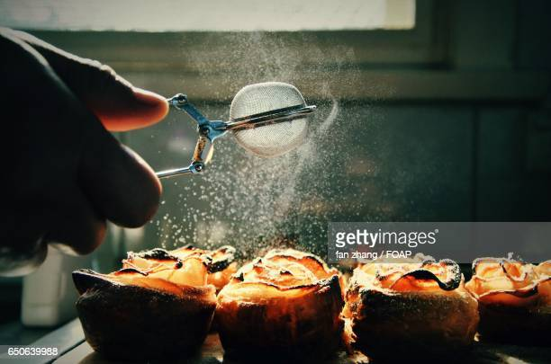 A person dusting sugar on baked food