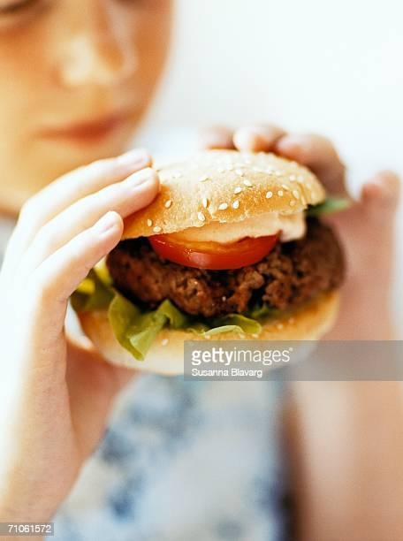 A person eating a hamburger.