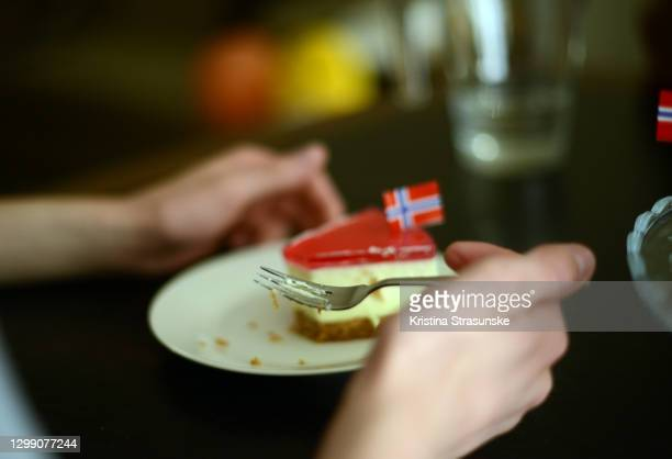 person eating cheesake decorated with norwegian flags - national holiday stock pictures, royalty-free photos & images