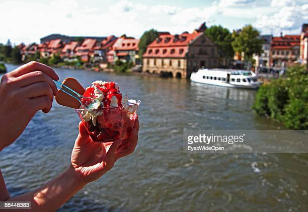 A person eating ice cream and a tourist boat on the river Regnitz on June 11 2009 in Bamberg Germany Bamberg is listed as a World Heritage by UNESCO