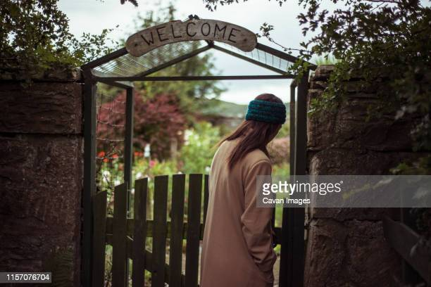 person enters lush garden gate with welcome sign - uncultivated stock pictures, royalty-free photos & images