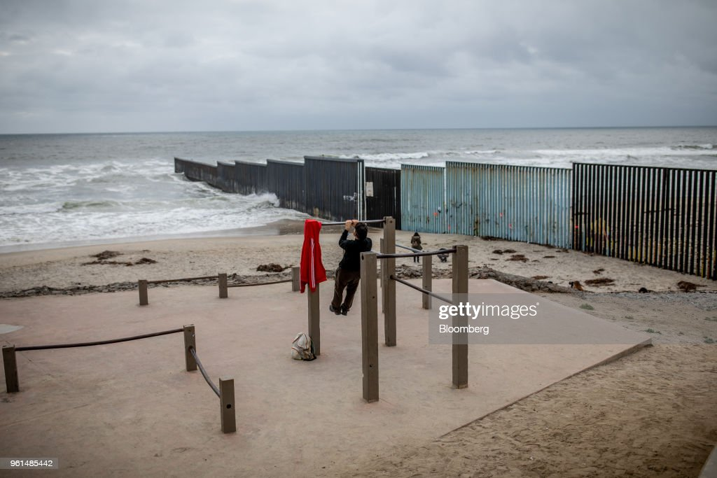 A person exercises in front of a section of a U.S.-Mexico border wall in Tijuana, Mexico, on Monday, May 21, 2018. 'We won't care about threats of a wall,' National Regeneration Movement Presidential candidate Andres Manuel Lopez Obrador announced, assuring another rally crowd in Zacatecas, one of the states that sends the most migrants to the U.S., that with him in power, they'll achieve equal footing with their neighbors to the north. Photographer: Alejandro Cegarra/Bloomberg via Getty Images