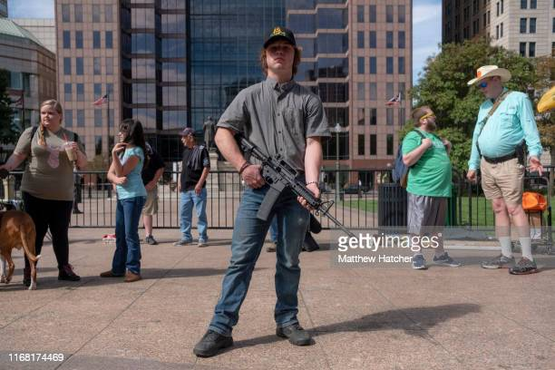Person exercises their right to open carry a firearm as gun owners and second amendment advocates gather at the Ohio State House to protest gun...