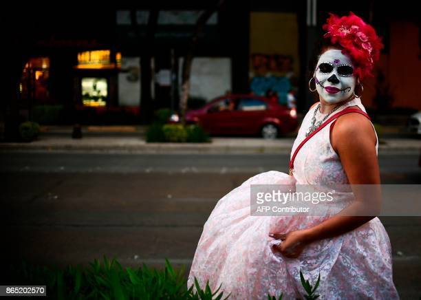 A person fancy dressed as Catrina takes part in the Catrinas Parade along Reforma Avenue in Mexico City on October 22 2017 Mexicans get ready to...