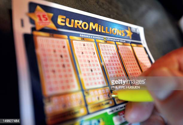 A person files a euromillions lottery grid on August 7 2012 in the northern city of Lille Millions of people from nine European countries are...