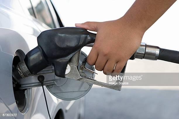 A person filling a petrol tank