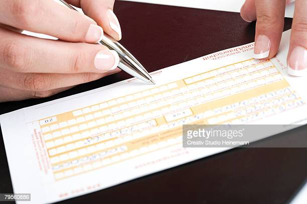 person filling in a money transfer form - money transfer stock pictures, royalty-free photos & images