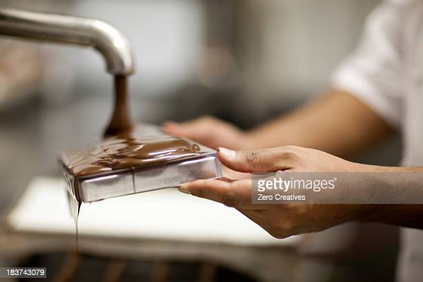 person filling mould with melted chocolate - chocolate making stock pictures, royalty-free photos & images