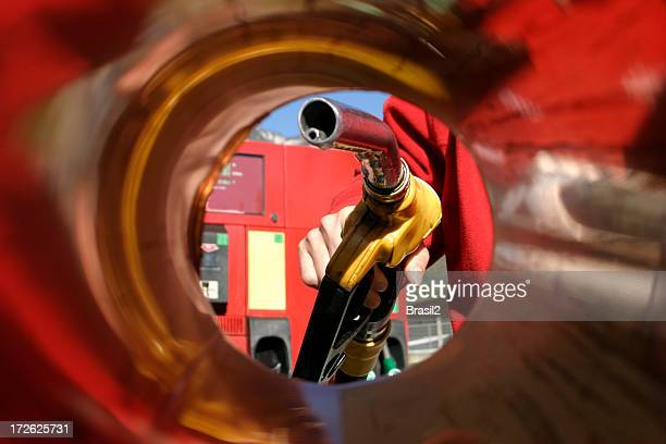 a person filling up the car in a gas station - gas tank stock photos and pictures