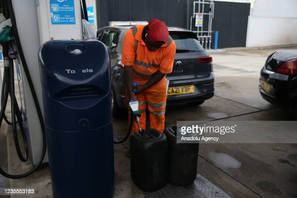 Person fills up a bin with fuel at a petrol station in London, United Kingdom on September 28, 2021. The UK has seen long queues formed in front of...