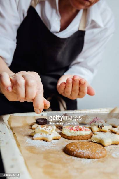 person finishing homemade cookies - fruit cake stock pictures, royalty-free photos & images