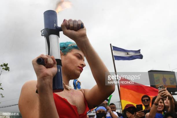 TOPSHOT A person fires a homemade mortar as he joins thousands of Nicaraguan antigovernment protesters including members of the Lesbian Gay Bisexual...
