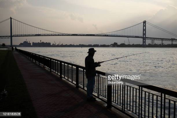 Person fishes in the Detroit River in front of Ambassador Bridge on the Canada-U.S. Border in Windsor, Ontario, Canada, on Thursday, Aug. 9, 2018....