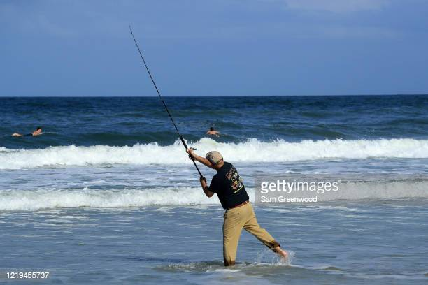 A person fishes in the surf on April 17 2020 in Jacksonville Beach Florida Jacksonville Mayor Lenny Curry announced Thursday that Duval County's...