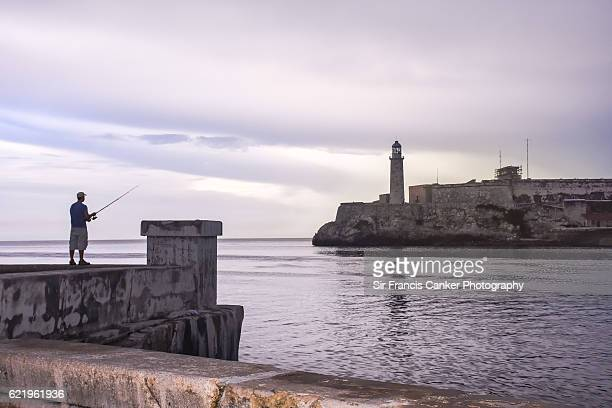 Person fishing at Havana's Malecon with Morro lighthouse on background at dusk, Cuba