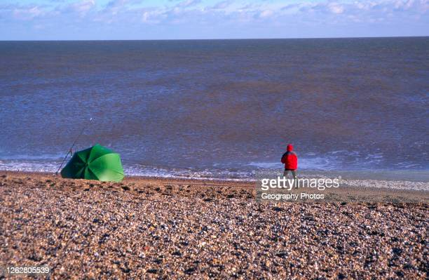 Person fishing from the beach on the North Sea coast, Shingle Street, Suffolk, England, UK.