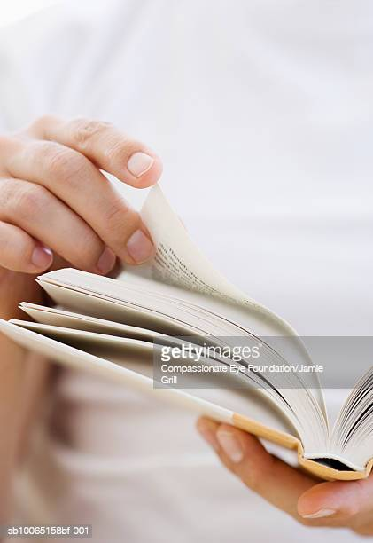 """person flipping through pages of book, close-up, mid section - """"compassionate eye"""" fotografías e imágenes de stock"""