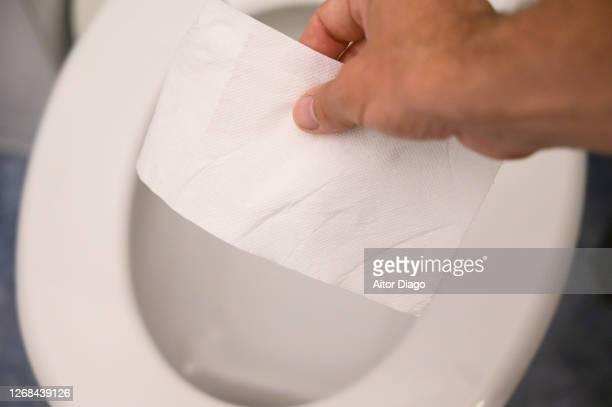 a person flushes a piece of toilet paper down the toilet and flushes the toilet. germany - cuvette photos et images de collection