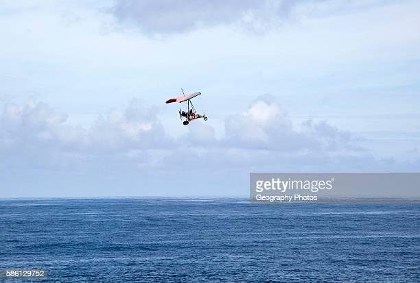 Person flying micro light plane over the ocean Caleta de Caballo Lanzarote Canary islands Spain