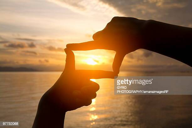 Person Framing Sunset with Fingers