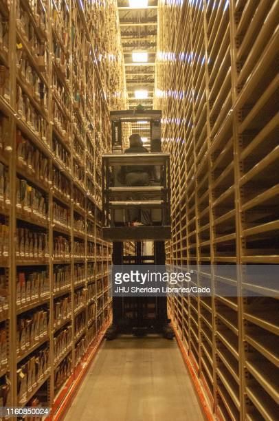 A person from the back drives a motorized lift through tall stacks of media in a storage facility of the Milton S Eisenhower Library at the Johns...