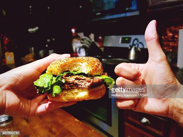 Person gesturing thumbs up while holding burger