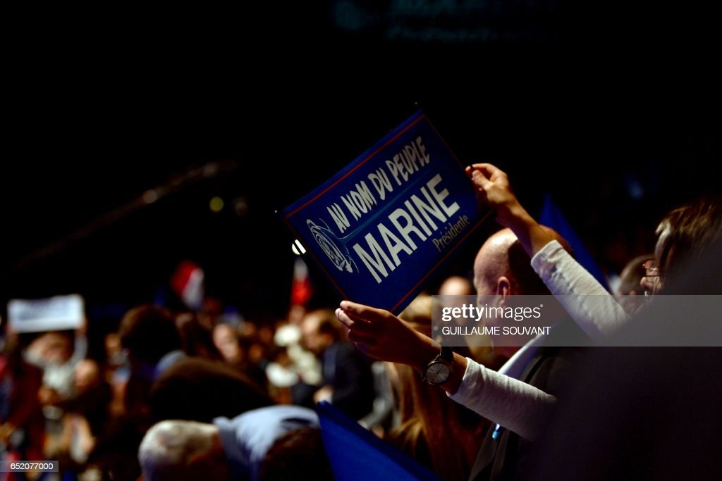 A person golds a placard which translates as 'In the name of the people, Marine' during a meeting of the French far-right Front National (FN) party candidate for the presidential election Marine le Pen on March 11, 2017 in Deols, central France. /