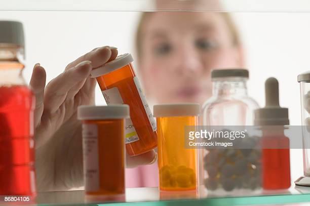 person grabbing bottle of medicine - armoire de toilette photos et images de collection