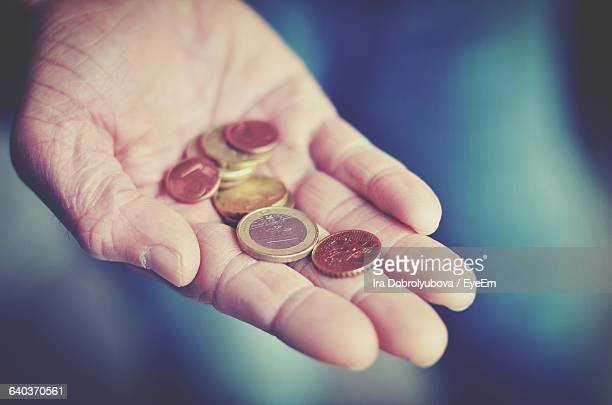 Person Hand Holding Currency Coins