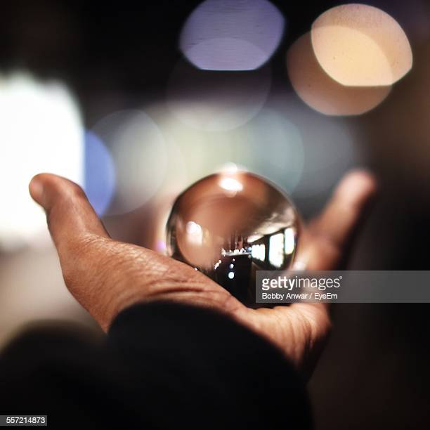 Person Hand Holding Reflection Of Restaurant In Glass Sphere