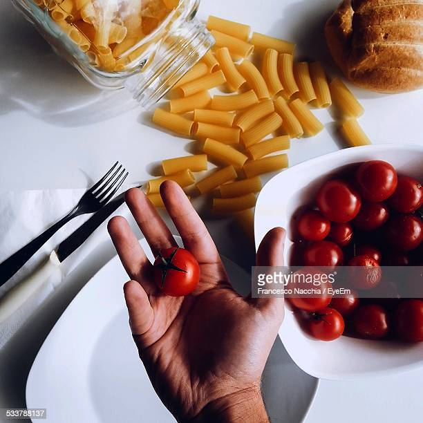 Person Hand Holding Tomato In Kitchen