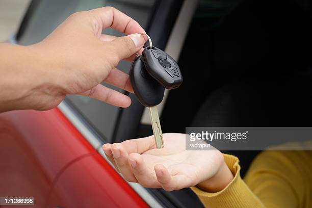 Person handing over car keys to a driver in a red car