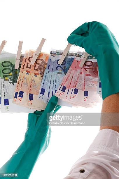 person hanging different euro notes on clothesline, close-up - money laundering stock photos and pictures