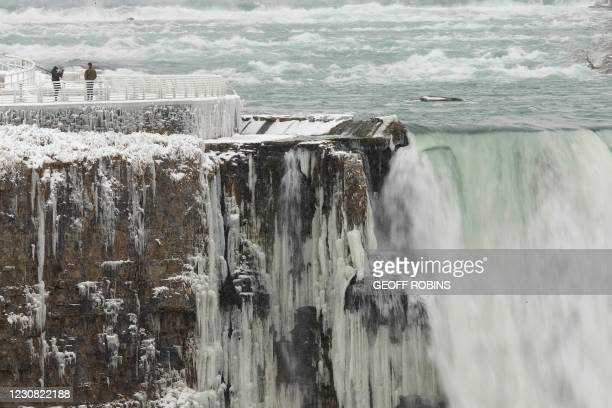 Person has their photo taken on the US side of the Horseshoe Falls in Niagara Falls, New York, on January 27 as taken taken from the Canadian side.