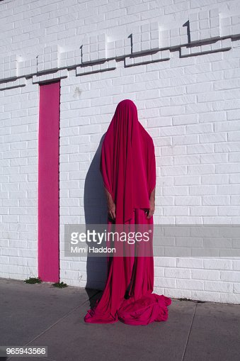 Person Hiding Under Pink Fabric Standing in Front of White Wall
