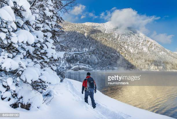 person hiking along a lake in winter