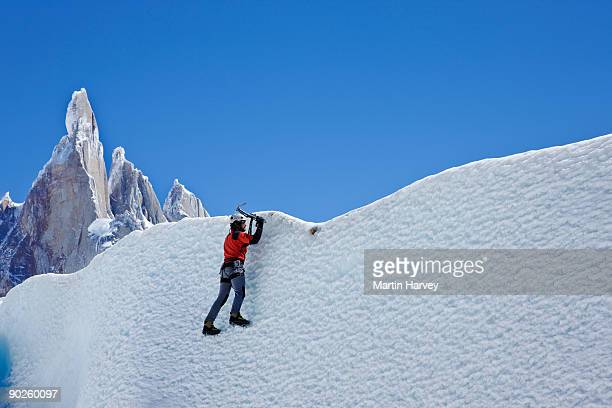 Person hiking and climbing frozen mountainside