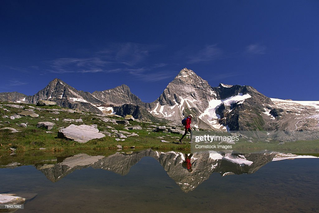 Person hiking by mountains : Stockfoto