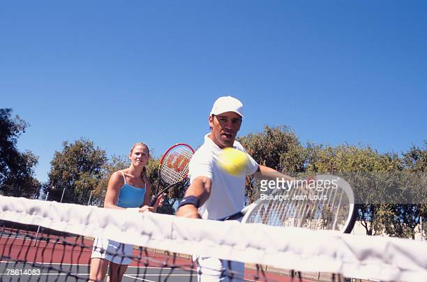 Person hitting tennis ball over net