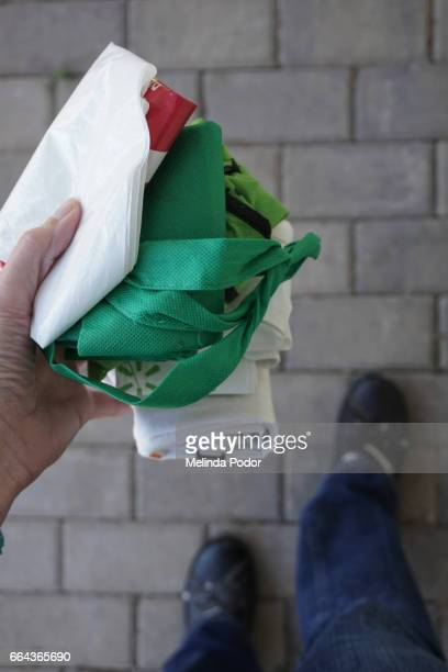 person holding a bunch of rolled-up reusable shopping bags