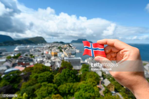 person holding a norwegian flag souvenir in alesund, norway. personal perspective. - norwegian flag stock pictures, royalty-free photos & images